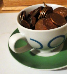 Teacup full of british copper coins 1p 2p