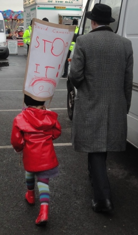 4yo and her Dad on the N30 march carrying a david cameron stop it homemade placard