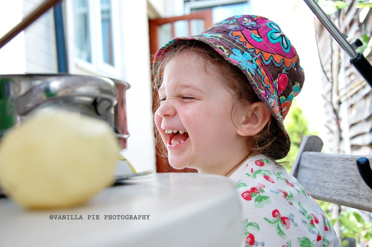 Child outside, peeling potatoes and laughing
