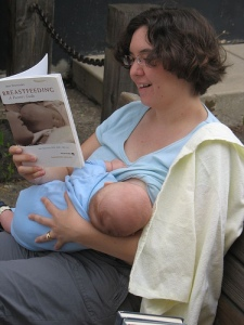 Breastfeeding mother reading a book