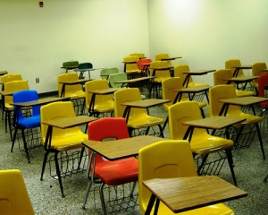 Rows of empty desks in a classroom.  Photo: evemaiden