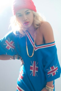 Rita Ora, promoting her new single RIP, wearing a loose blue dress featuring the union jack